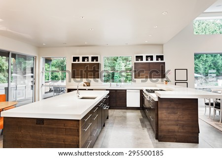 Kitchen with Island, Sink, Cabinets, and Hardwood Floors in New Luxury Home - stock photo