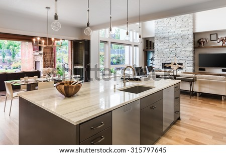 Kitchen with Island, Sink, Cabinets, and Hardwood Floors in New Luxury Home, with View of Living Room, Dining Room, and Outdoor Patio - stock photo