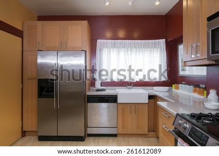 Kitchen with light wooden cabinets and dark red wall paint.  - stock photo