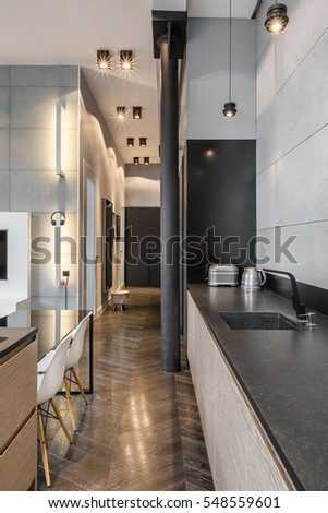 Kitchen with long, elegant, black countertop and table with white chairs