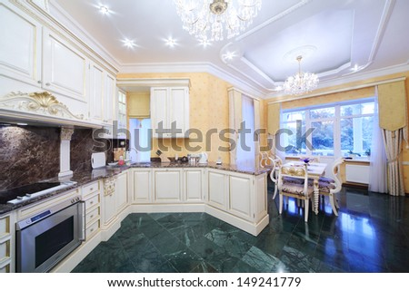 Kitchen with luxury furniture in classic style, green marble floor. - stock photo
