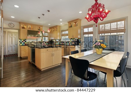 Kitchen with oak cabinetry and colored tile backsplash - stock photo