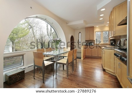 Kitchen with oak cabinets and window arch - stock photo