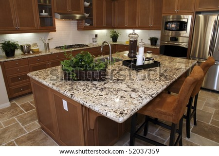 Kitchen with stainless steel appliances and a granite island. - stock photo
