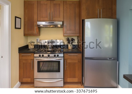 Kitchen with stainless steel appliances with wooden floor - home interior design. - stock photo