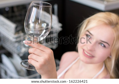 Kitchen Woman. Girl in the kitchen using dishwasher. view of young woman in kitchen doing housework. see clean the glass - stock photo