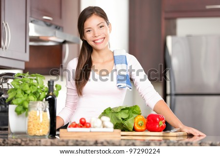 kitchen woman making healthy food standing happy smiling in kitchen preparing salad. Beautiful cheerful multicultural Chinese Asian / Caucasian young woman at home.