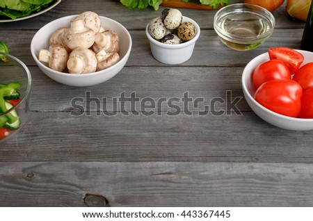 Kitchen wooden table with ingredients for cooking healthy and tasty food with copy space. Mushrooms, tomatoes, quail eggs, pepper, cucumber and olive oil on wooden table - stock photo