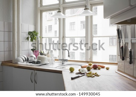 Kitchen worktop with chopped fruit and vegetables in urban apartment - stock photo
