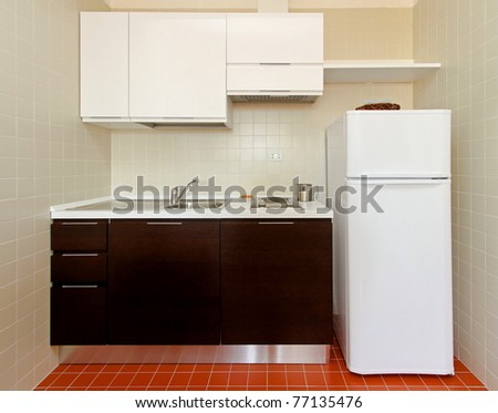 Kitchenette with all appliances in small apartment - stock photo