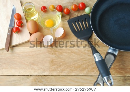 kitchenware are including frying pan, flipper used in frying, spoon, fork, knife, wooden block, eggs and fresh tomatoes with oil in glass container are placed on a wooden background in top view. - stock photo