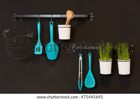 Kitchenware hanging in a black wall