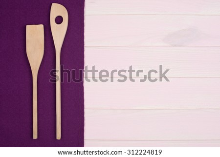 Kitchenware on purple towel over wooden kitchen table. View from above.