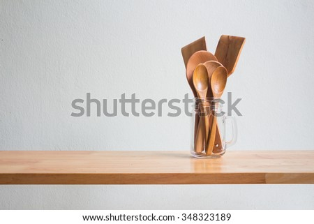 Kitchenware with wooden ladle and wooden spoon in glass jug on wooden table over white wall background - stock photo