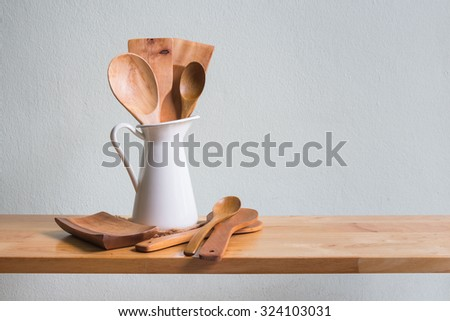 Kitchenware with wooden ladle and wooden spoon in white vase on wooden table over white wall background - stock photo
