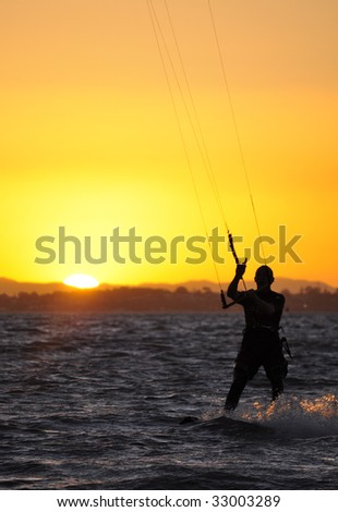 Kite boarder at sunset - stock photo