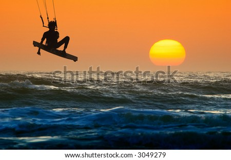kite boarder in action and sunset - stock photo