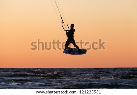 kite boarding aerial jump silhouette, with sunset background. - stock photo