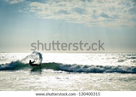 KITE BOARDING. Kite surfer in waves. - stock photo