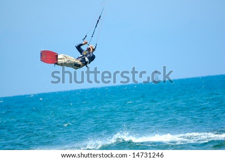 kite boarding on a beach of sea, sportsmen in action - stock photo