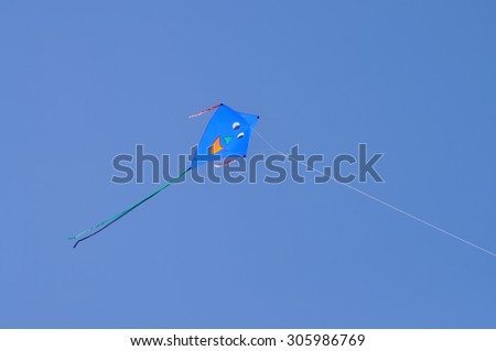 Kite flying in a blue sky - stock photo