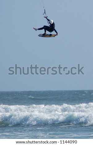 Kite surfer ( kite boarder ) defies gravity high above the waves near Cayucos, California