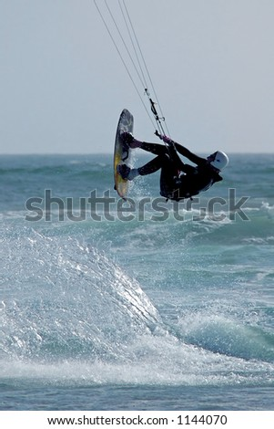 Kite surfer ( kite boarder ) jumping the waves near Cayucos, California