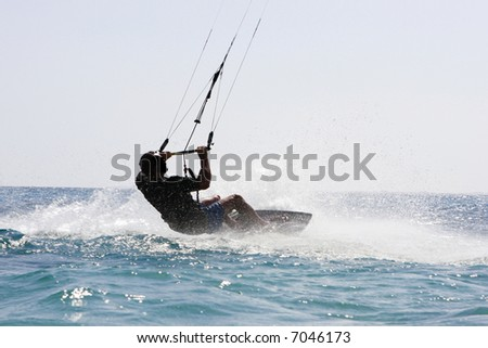 Kite surfer landing in water with huge splash - stock photo