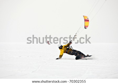 Kite surfer ride on snowboard. Snowkiting in the snow on frozen lake.