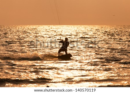 Kite surfer sailing in the sunset sea  - stock photo
