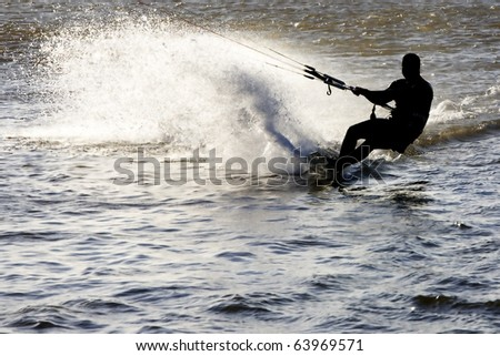 Kite surfer silhouette, sliding fast with a massive spilled water fan, at the Obidos lagoon, Bom Sucesso, Foz do Arelho, Silver Coast, Portugal - stock photo
