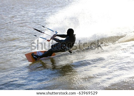 Kite surfer sliding fast with a massive drag water fan, at the Obidos lagoon, Bom Sucesso, Foz do Arelho, Silver Coast, Portugal - stock photo
