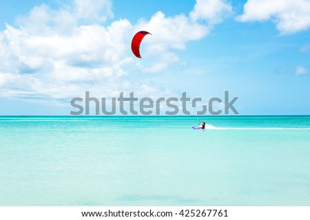 Kite surfer surfing on the Caribbean Sea at Aruba island - stock photo