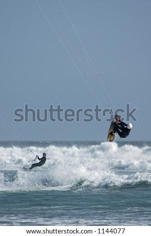 Kite surfers ( kite boardesr ) riding and jumping the waves near Cayucos, California. - stock photo