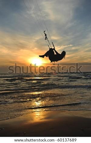 kite surfing in sunset - stock photo