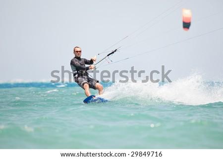 Kiteboarder enjoy surfing in blue water - stock photo