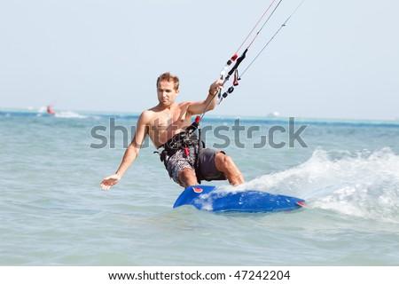 Kiteboarder enjoy surfing in blue water. - stock photo