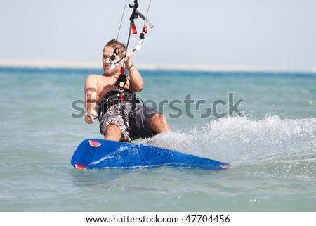 Kiteboarder enjoying surfing in blue water. - stock photo