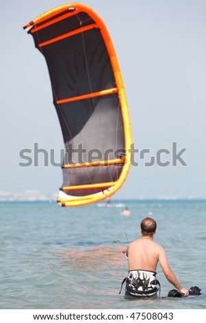 Kiteboarder lifting kite in the airenjoy surfing in blue water. - stock photo