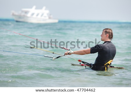Kiteboarder standing in water and watching kite - stock photo