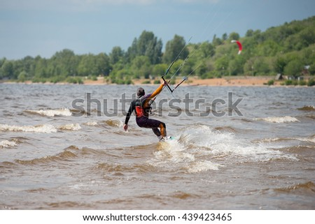 Kiteboarding.  A kite surfer rides the waves - stock photo