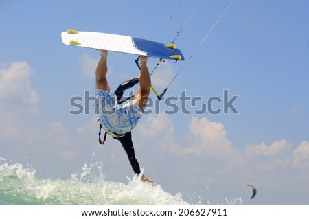 Kiteboarding in  a sunny summer day on  a Mediterranean sea coast - stock photo