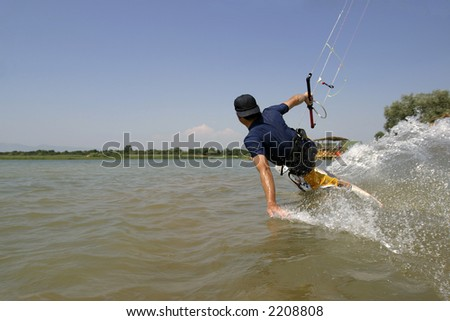 kitesurfer carving his board across the water - stock photo