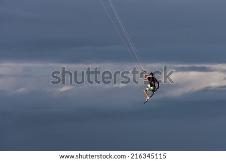 Kitesurfer jumping in the clouds - stock photo