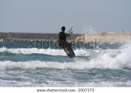kitesurfer jumping over the wave - stock photo