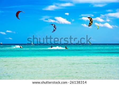 Kitesurfers at high speed around the beach Cinta, Sardinia - stock photo