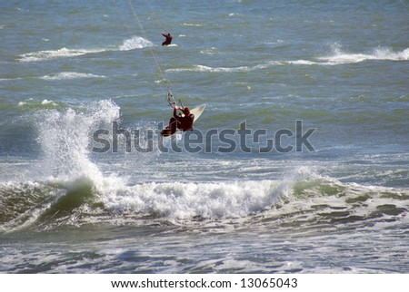 Kitesurfers enjoy a brisk breeze off the beach.