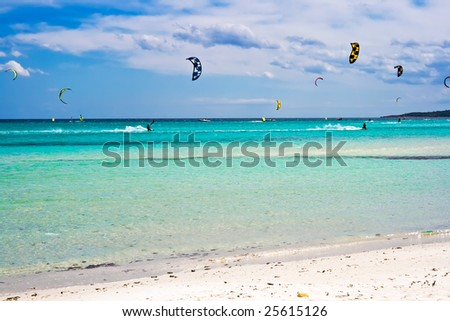kitesurfers gliding at high speed around the beach la Cinta, Sardinia - stock photo
