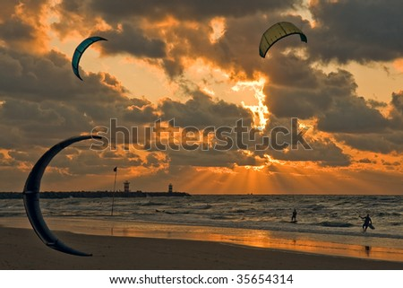 Kitesurfing in the evening at a Dutch beach - stock photo