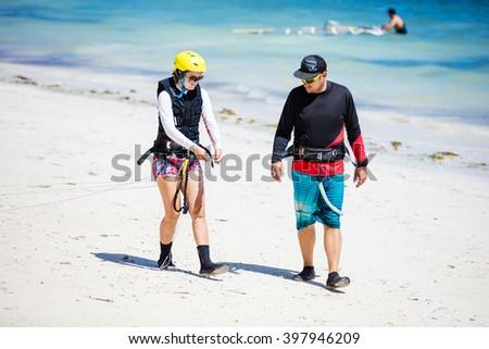 Kitesurfing instructor and female student preparing lines on beach - stock photo